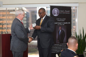 CGSC Foundation President/CEO Doug Tystad presents Gen. Lloyd J. Austin III, U.S. Army, Ret., with a Colin L. Powell Lecture Series silver commemorative coin for his support of the program.